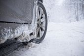 stock photo of slippery-roads  - Winter tire on snow-covered road. Landscape forest