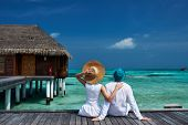 picture of couple sitting beach  - Couple on a tropical beach jetty at Maldives - JPG