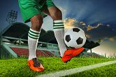 image of legs feet  - foot ball player holding foot ball on leg ankle on soccer sport field agianst stadium and dusky sky use for soccer footbal teaml competition - JPG