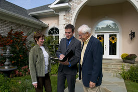 stock photo of real-estate agent  - real estate agent showing a new home to a senior couple - JPG