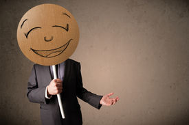 stock photo of emoticon  - Businessman holding a cardboard smiley face emoticon in front of his head - JPG