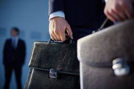pic of politician  - Cropped image of business partners carrying briefcases on the foreground while their colleague standing on the background  - JPG