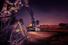 stock photo of power-shovel  - A large construction excavator late at night - JPG