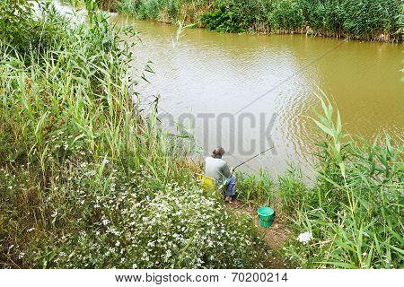 Fisherman Is Fishing On Riverbank