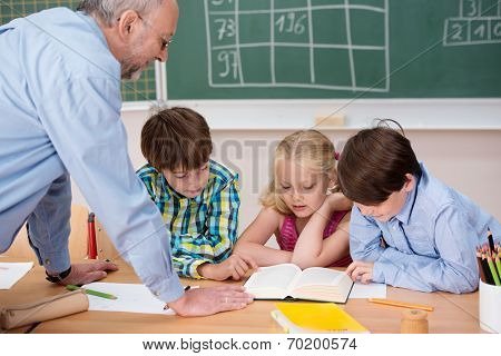Three Young Children Studying In Class