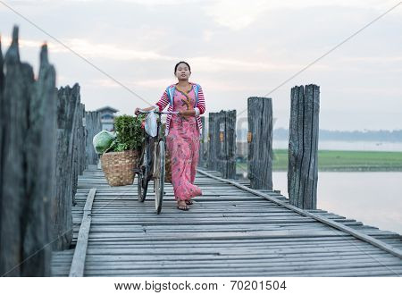MANDALAY, MYANMAR - JAN 19, 2014: Unidentified young woman in traditional dress crossing U Bein bridge with bicycle loaded with personal goods. Longest teak wooden bridge attracts many tourists