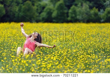 Beautiful young woman stretching her arms high in the air with a smile of pleasure and satisfaction as she sits in a rural meadow full of colorful yellow flowers, with copyspace