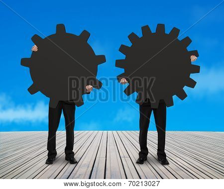 Two Men Holding Their Different Gear With Sky Background