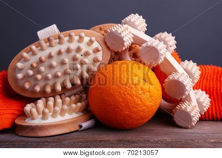 Roller brush, towel, orange and oval brushes on wooden table on dark grey background