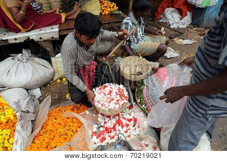 KOKATA, INDIA - FEBRUARY 15: People buying and selling flowers and garlands at the flower market next to a railway track on February 15, 2014 in Kolkata (Calcutta), West Bengal, India