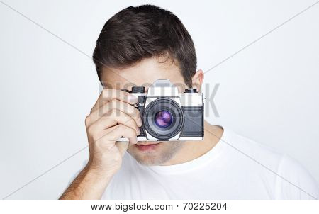 Close-up of a young man using a retro camera against gray background