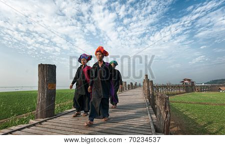 MANDALAY, MYANMAR - JAN 19, 2014: Unidentified Burmese women in traditional clothes visiting U Bein bridge and local Buddhist temple. Domestic tourism is important part of life for people of Myanmar