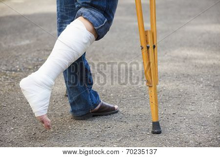 Asian Young Man On Crutches With Tree Background