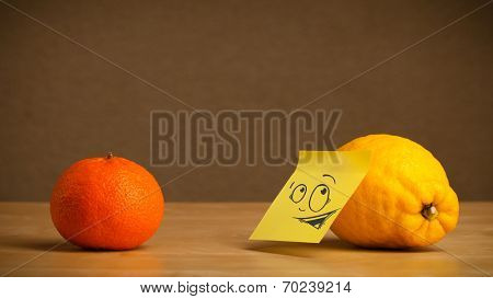 Lemon with sticky post-it note reacting at orange