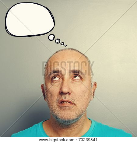 portrait of displeased senior man looking up at empty speech balloon over grey background
