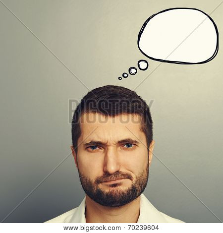 displeased young man with drawing speech bubble over grey background