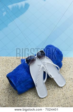 White Sandals And Sunglasses With Blue Towel Near Water Of Swimm
