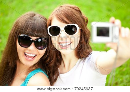 Selfie. Two young trendy girls doing selfie. A couple of friends photographing themselves. Two women did a photo shoot in nature.