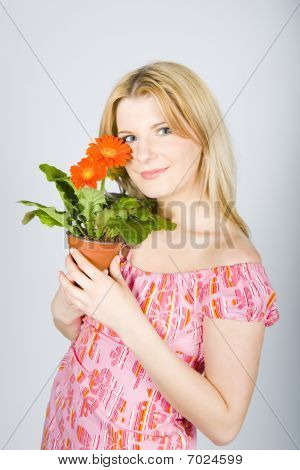 young beautiful spring woman with flowers in pot