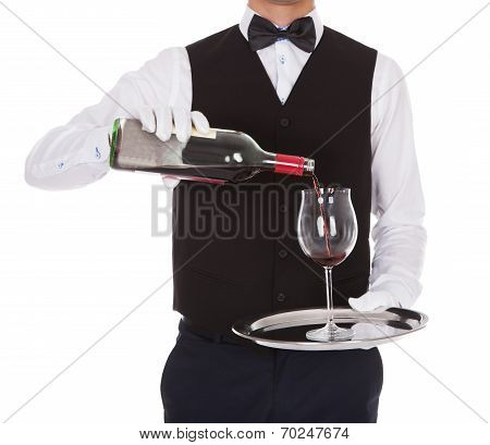 Waiter Serving Red Wine In Glass