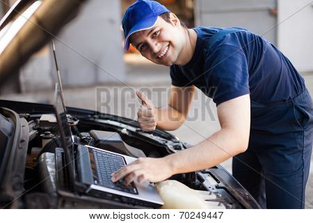 Smiling mechanic using a laptop computer to check a car engine