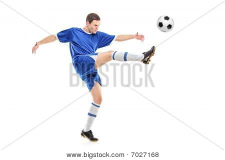 A soccer player shooting a ball