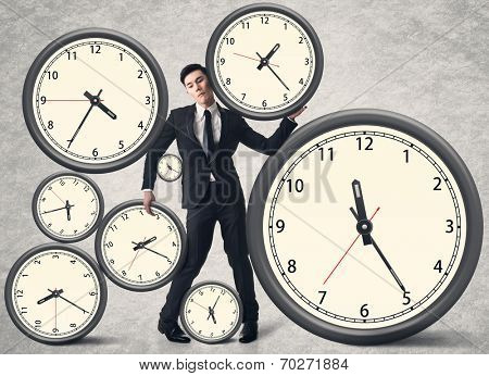 Time pressure concept, Asian business man with many clocks.