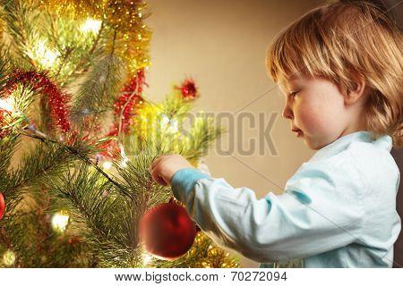 boy hangs Christmas toy