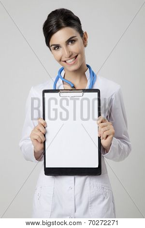 Smiling medical doctor woman with empty blank in hands.