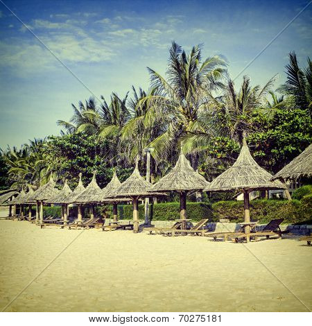 Straw sunshades and chaise longue on the tropical beach. Toned photo.