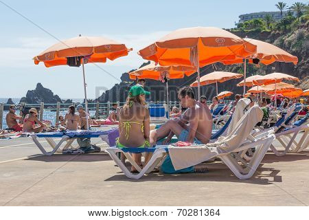 People Sitting Under A Parasol At A Public Swimming Bath At Madeira, Portugal
