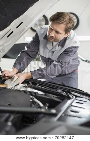 Male mechanic repairing car engine in workshop