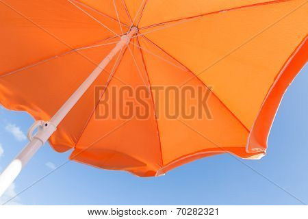 Bottom View Of Orange Parasol Against A Blue Sky