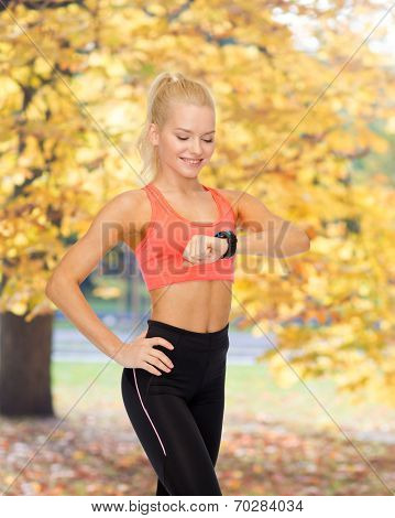 fitness, technology and exercising concept - smiling woman looking at heart rate monitor on hand