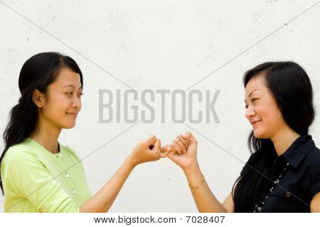 Two Happy Girls Make Peace To Each Other