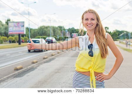 Beautiful Woman Hitch-hiking On The Roadside.