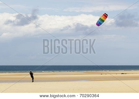 Man playing with a kite at the beach