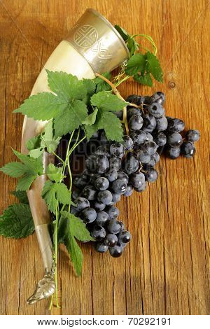 Brush ripe sweet grapes with a traditional drinking horn on wooden background
