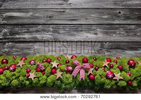 Wooden Christmas Background With Green Moos And Red Balls.