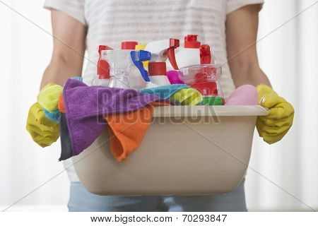 Midsection of woman carrying basket of cleaning supplies