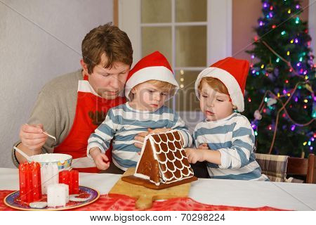 Father And Two Little Sons Decorating A Gingerbread Cookie House