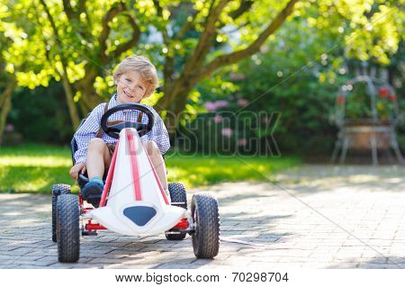 Active Little Boy Driving Pedal Car In Summer Garden