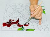 image of batik  - Artist carefully paint the floral flower image on a white batik fabric - JPG