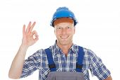 picture of electrician  - Portrait of smiling mid adult electrician showing okay gesture over white background - JPG