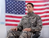 stock photo of soldier  - Cropped image of patriotic soldier sitting on wheel chair against American flag - JPG