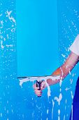 stock photo of janitor  - Cropped image male servant cleaning glass with squeegee over blue background - JPG