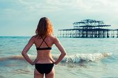 picture of derelict  - A young woman wearing a swimsuit is on the beach and is looking at a derelict pier - JPG