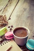 stock photo of sketch book  - macaroons espresso coffee cup and sketch book on wooden rustic table vintage stylized photo - JPG