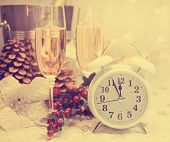 stock photo of midnight  - Happy New Year table setting with white retro clock showing five to midnight with champagne and festive decorations against white starry background with bokeh lights with retro vintage filter - JPG