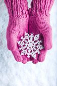 picture of knitting  - Woman hands in light pink knitted mittens with sparkling wonderful snowflake on a white snow background - JPG